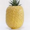 Immagine di ananas in ceramica color giallo su sfondo bianco.
