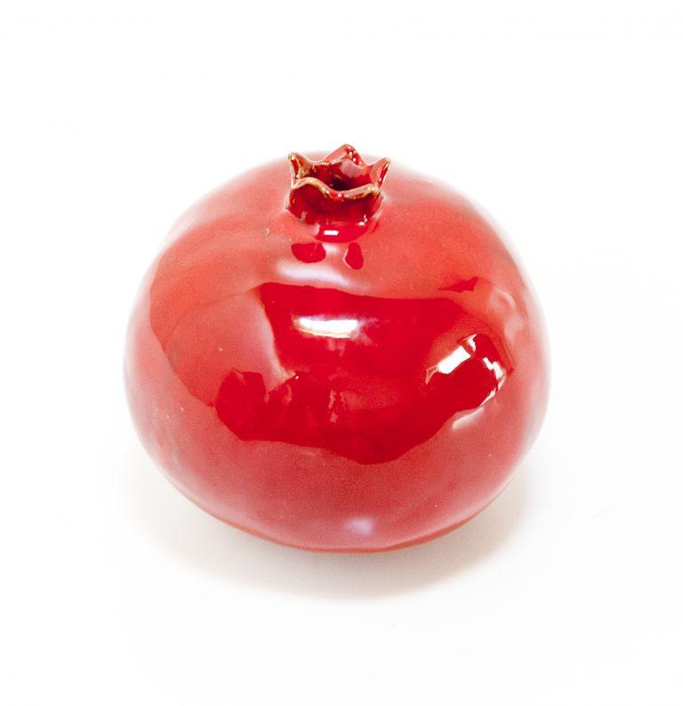 Immagine di melagrana di ceramica colore rosso su sfondo bianco