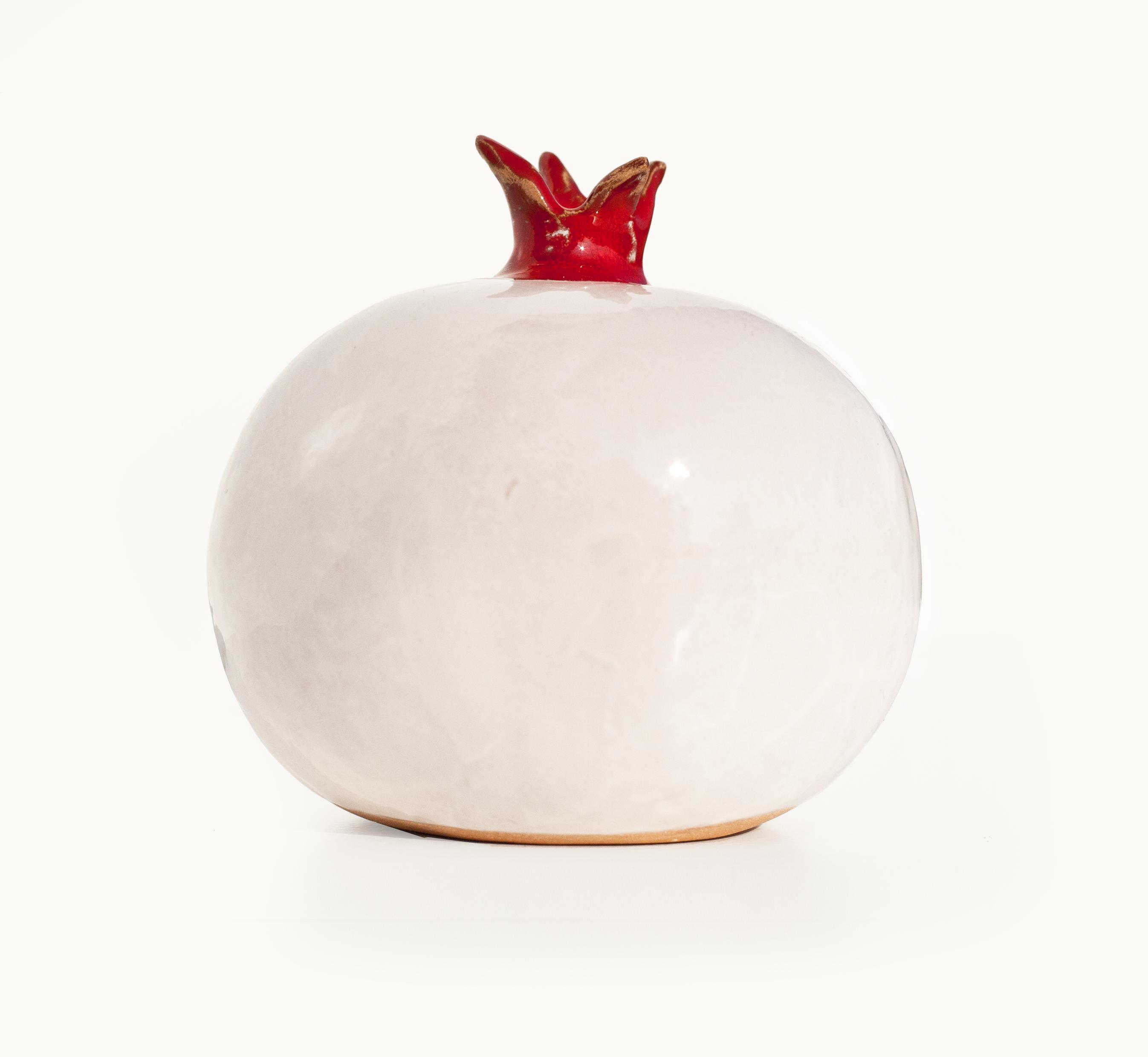 Immagine di melagrana di ceramica colore bianco e rosso su sfondo bianco