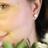 Coppia di orecchini cuore indossati. Orecchini fatti a mano in ceramica e lustro oro.