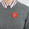 Immagine di spilla Papavero artigianale in ceramica di colore rosso vivo. Spilla indossata su maglia spinata di colore grigio.