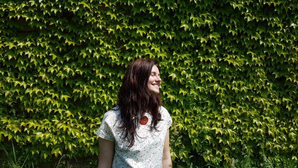 Ragazza che indossa girocollo papavero rosso collana Anseo, sfondo di edera.