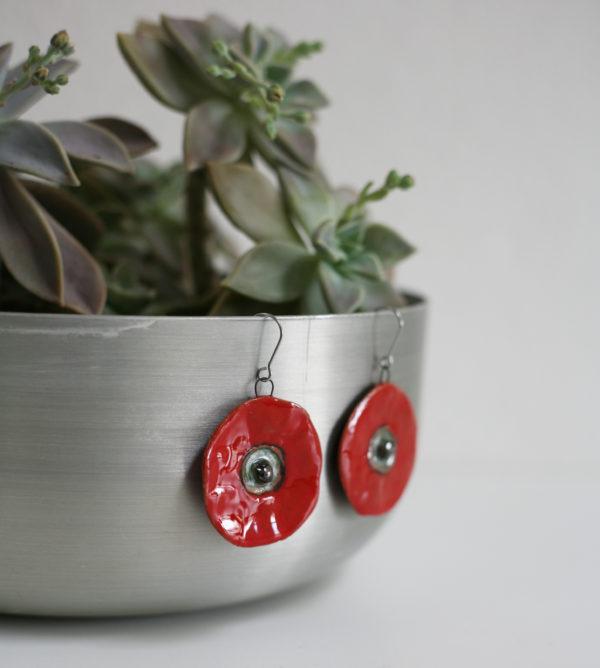 Orecchini Papavero pendenti gioielli artigianali in ceramica colore rosso acceso. appesi su un vaso in acciaio.