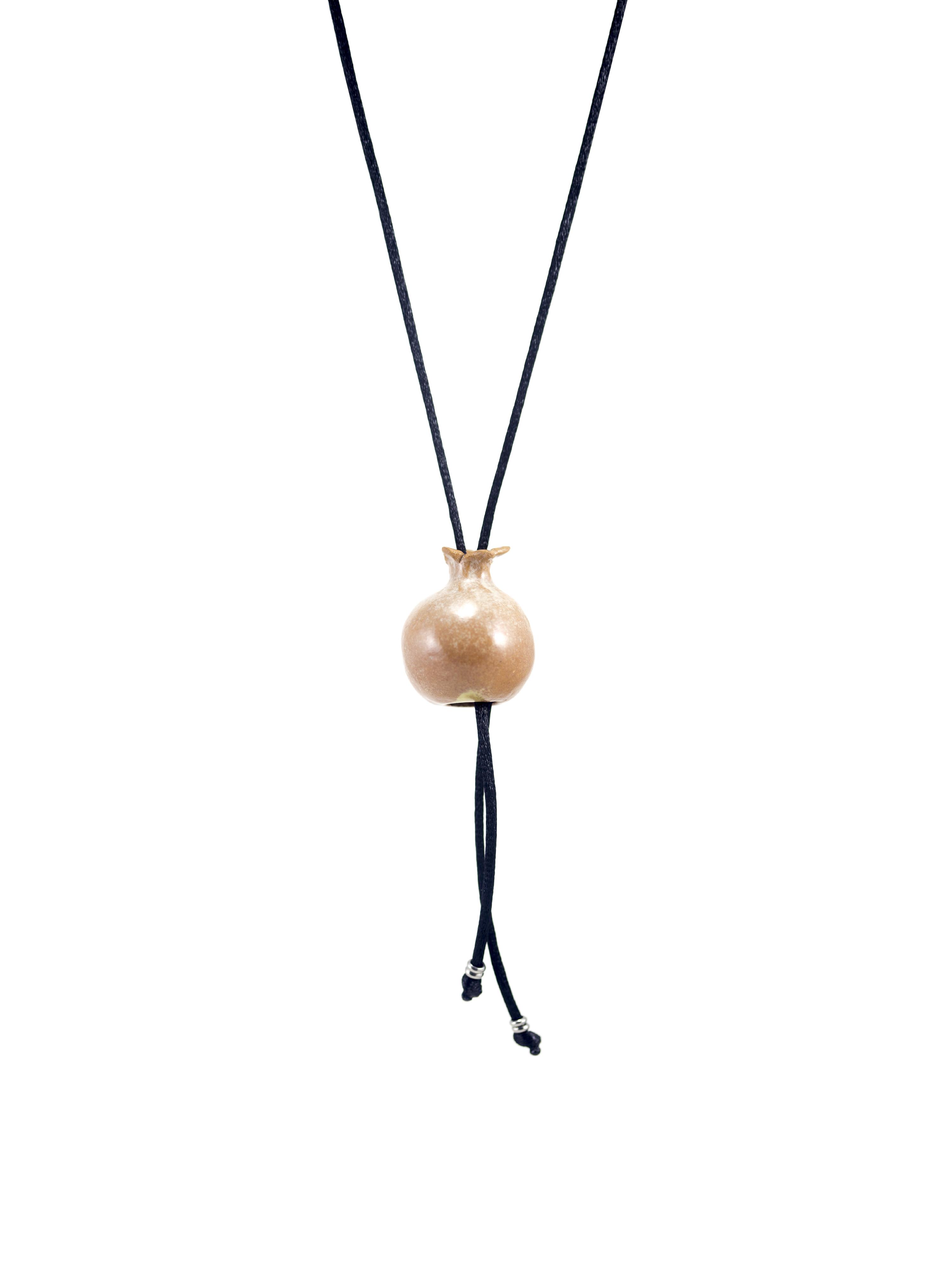 Immagine di mini melagrana gioiello portafortuna collana artigianato con ciondolo in ceramica fatto a mano a forma di piccola melagrana. Colore naturale, sfondo bianco.