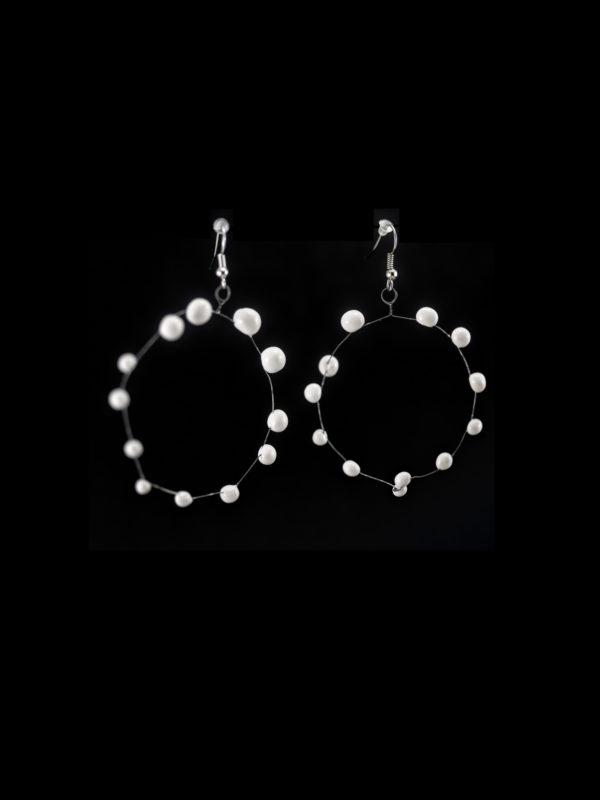 Coppia di orecchini a cerchio in ceramica e metallo, leggerissimi. Colore bianco su sfondo nero.