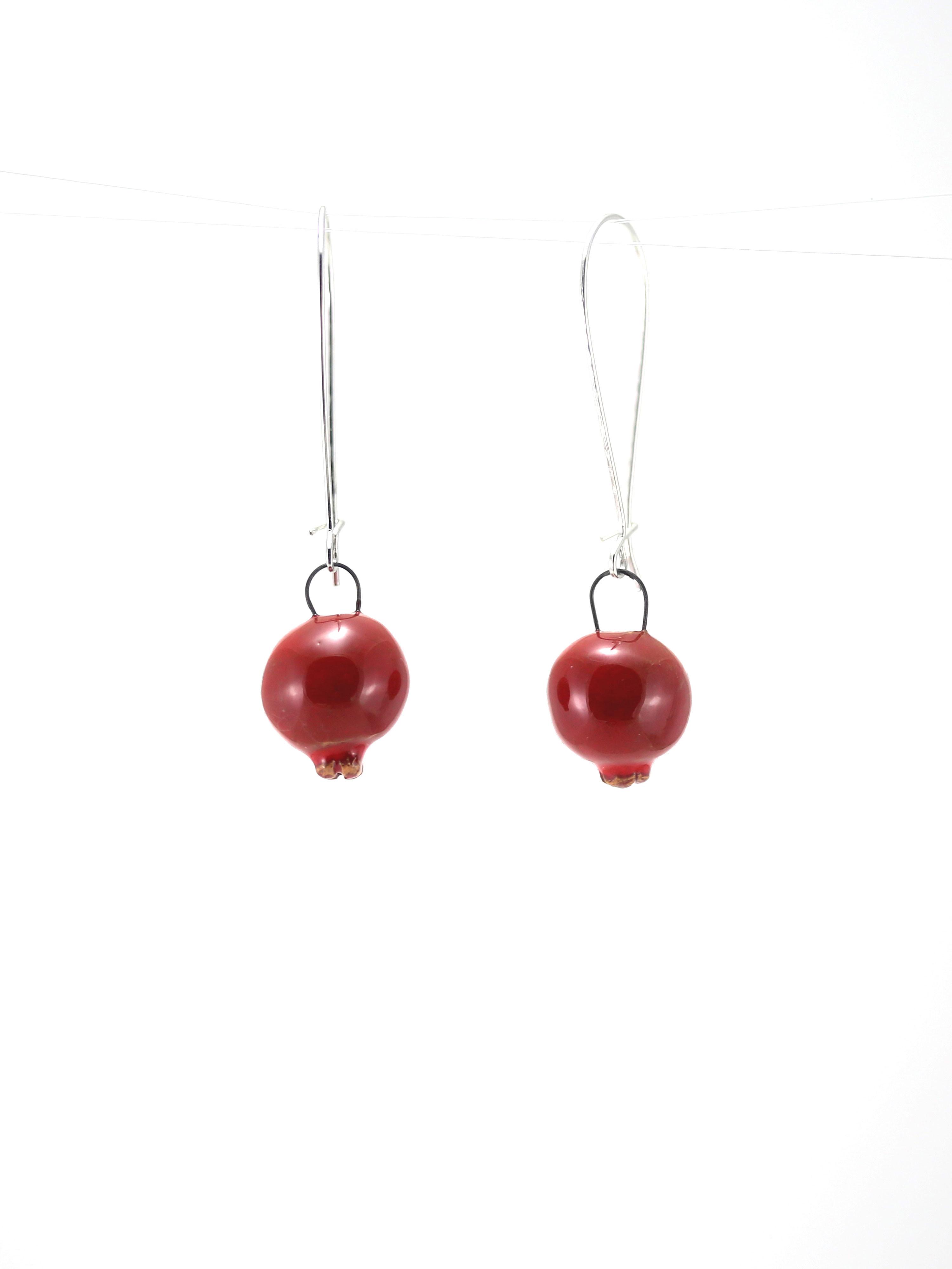 Immagine di orecchini melagrana pendenti colore rosso su sfondo bianco. Orecchini artigianali in ceramica