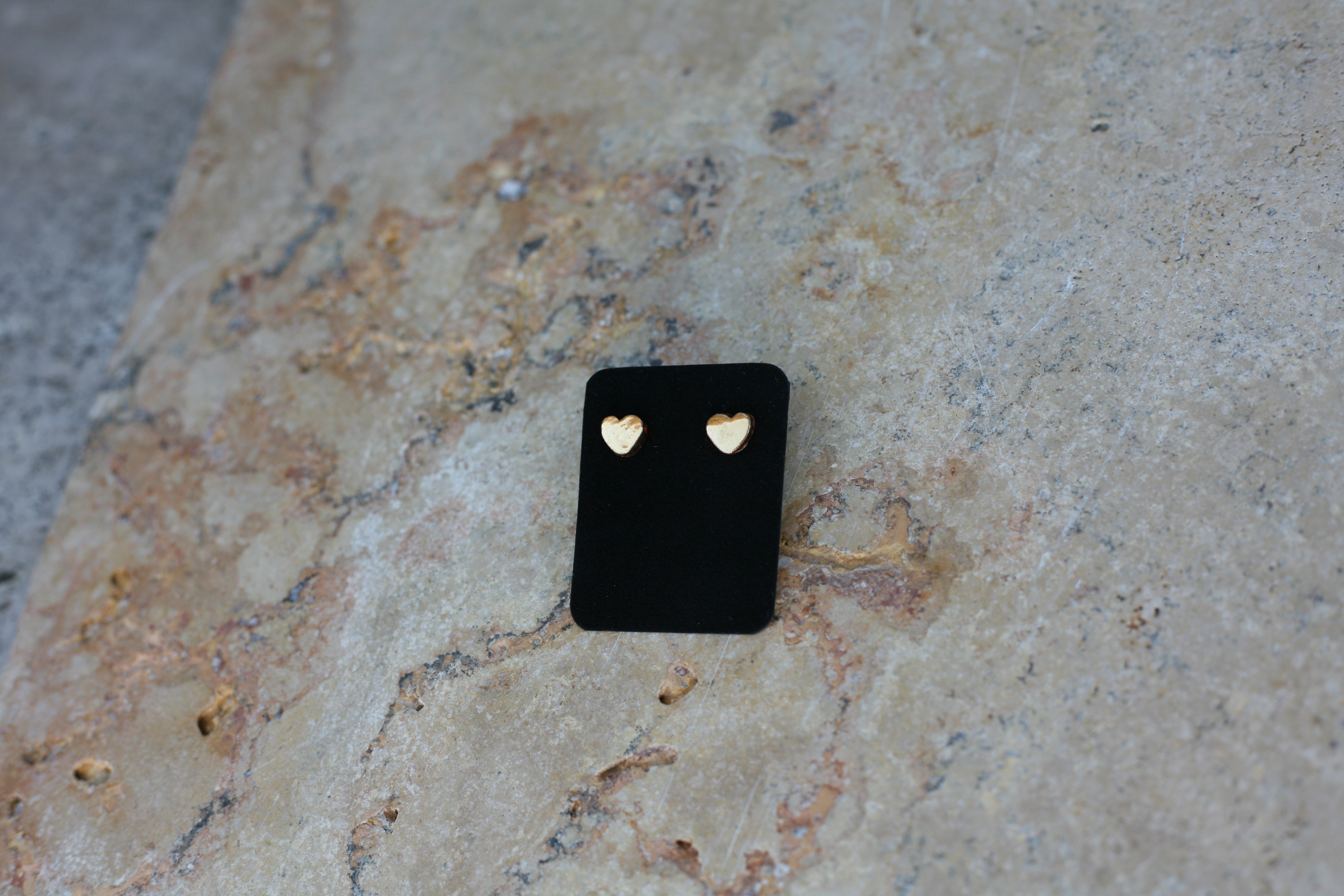 Coppia di orecchini a forma di cuore fatti a mano in ceramica e lustro oro su supporto in velluto nero e sfondo pietra.