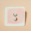 Orecchini Luna crescente Luna calante in porcellana e dettagli in lustro oro. Orecchini luna artigianale su supporto fatto a mano in acquerello su carta su sfondo rosa.