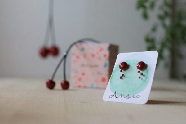 Immagine di set di collane ciliegia in ceramica Anseo e orecchini Kleinia Anseo su sfondo legno