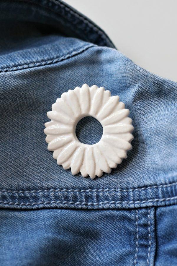 immagine di spila corolla in ceramica bianca su jeans blu