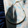 immagine di collana marina in porcellana e ottone su tessuto