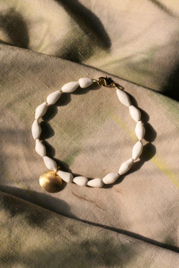 immagine di bracciale Marina in porcellana e ottone su sfondo color sabbia di mare